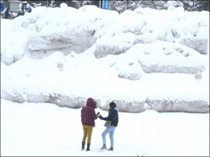 市役所駐車場(雪よけ後の雪景を写真で撮るタイからの旅行者)