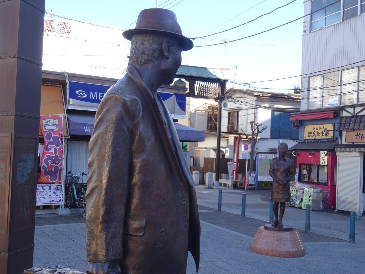 柴又駅前の寅さん像と今年3月にできたばかりのさくら像。