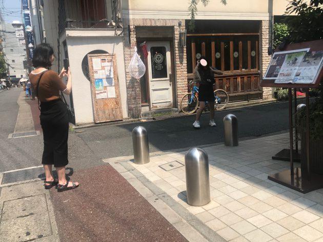 ▲今年6月20日に福岡市の中心部・大名の路地裏の何気ない場所で写真を撮影する韓国人旅行者